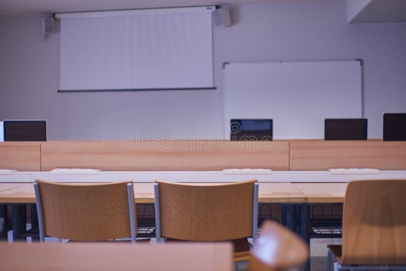 Sala de clase vacía, con las sillas, las tablas, con los ordenadores y la pantalla de proyector imagen de archivo