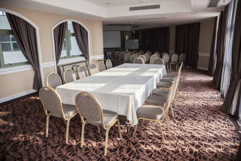 Sala de conferências vazia com tela da apresentação e a tabela longa. fotos de stock