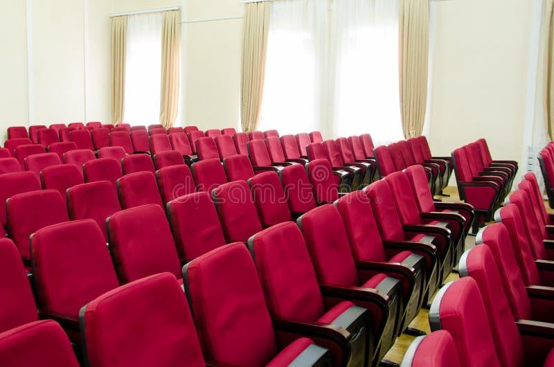 Sala de conferencias con las sillas cómodas rojas y paredes beige con las cortinas en las ventanas fotografía de archivo libre de regalías