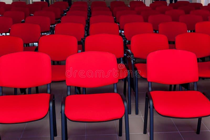 Sala de conferencias con una etapa roja y las sillas imagenes de archivo