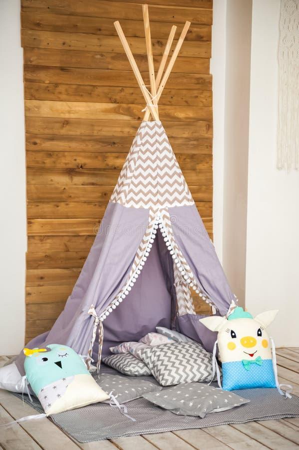 A sala de crianças em um estilo rústico Tenda azul em uma sala de crianças Detalhes interiores de um berçário escandinavo brilhan foto de stock royalty free