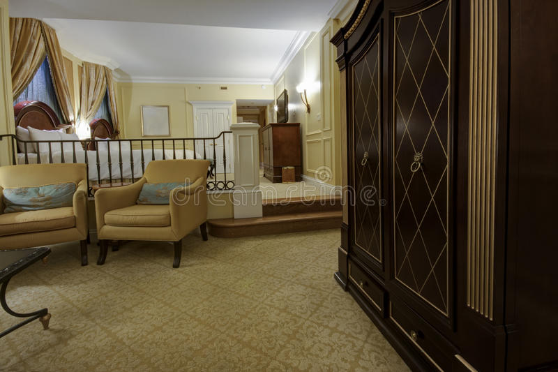 Sala de dois níveis clássica com poltronas, aparelho de televisão e cama fotografia de stock royalty free