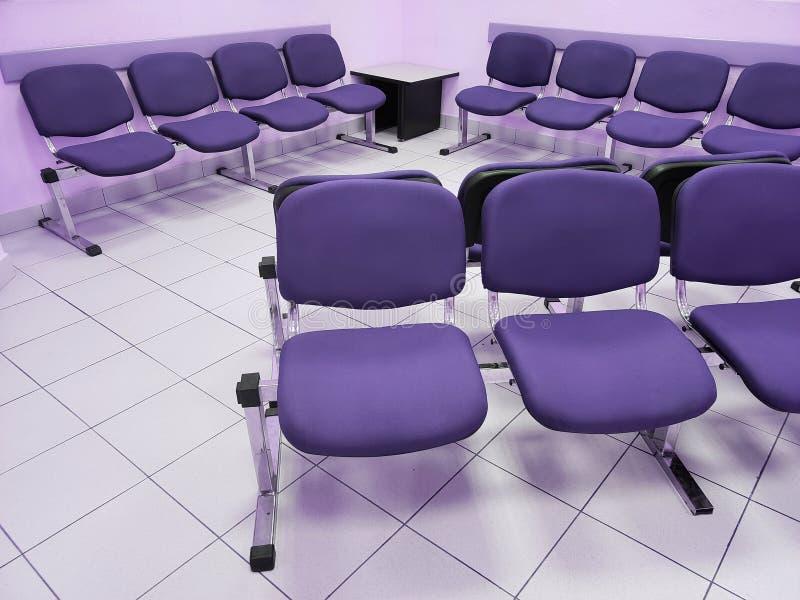 sala de espera com paredes violetas, o assoalho branco e as cadeiras confortáveis no roxo fotografia de stock royalty free