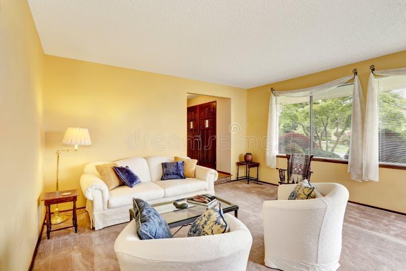 Sala de estar acogedora con las paredes amarillas claras y for Muebles oscuros paredes claras