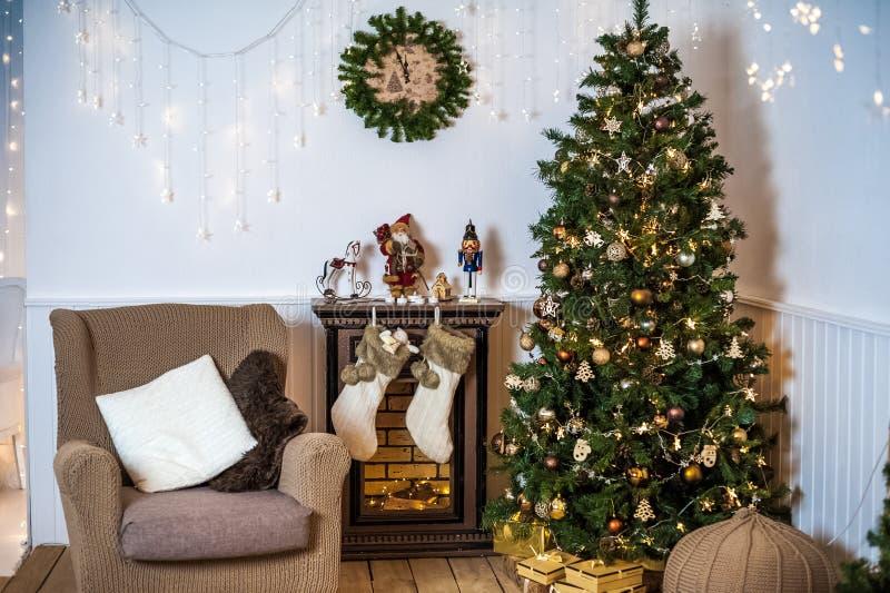 Sala de estar adornada por la Navidad o el Año Nuevo Butaca con la tela escocesa hecha punto, taburete, chimenea, árbol, interior imagen de archivo libre de regalías