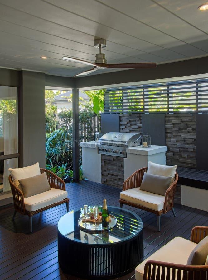 Sala de estar al aire libre con la tabla del Bbq y entarimados de madera de las sillas imágenes de archivo libres de regalías