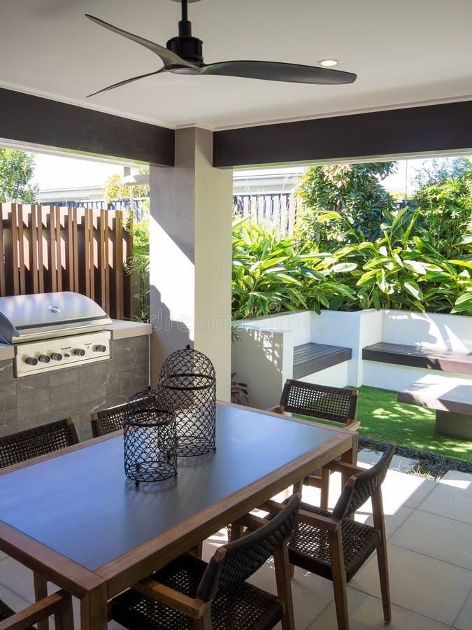 Sala de estar al aire libre del patio trasero con imagen vertical de la tabla y de las sillas imagenes de archivo