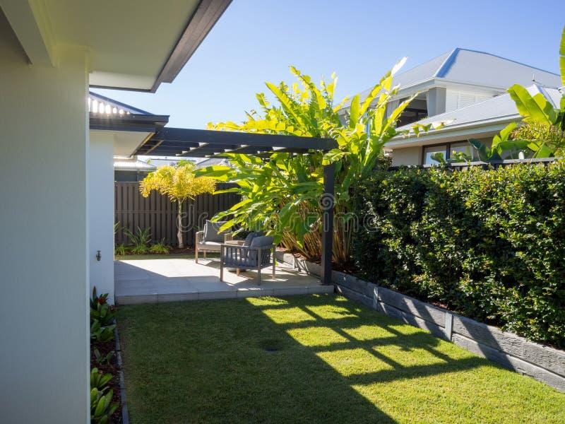 Sala de estar al aire libre de la pérgola del patio trasero con las plantas tropicales de los borrachines foto de archivo libre de regalías