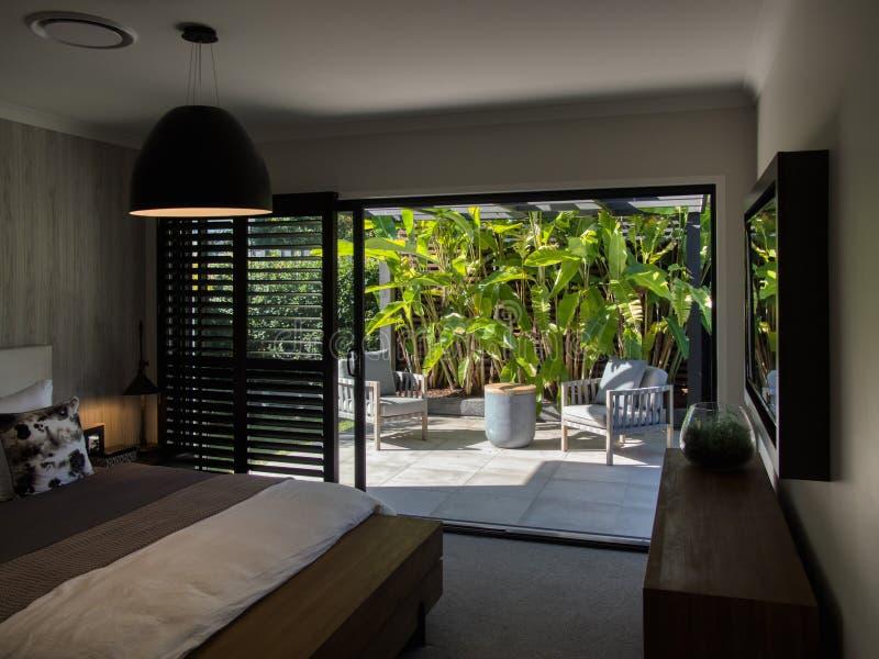 Sala de estar al aire libre de la pérgola del patio trasero con las sillas cómodas y la planta tropical de los borrachines fotos de archivo