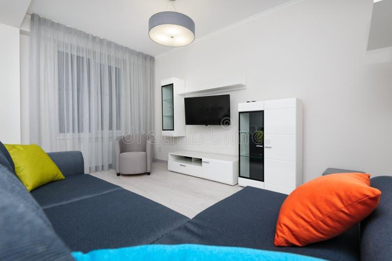 Sala de estar blanca con el aparato de TV, la silla y el sofá gris imagen de archivo libre de regalías