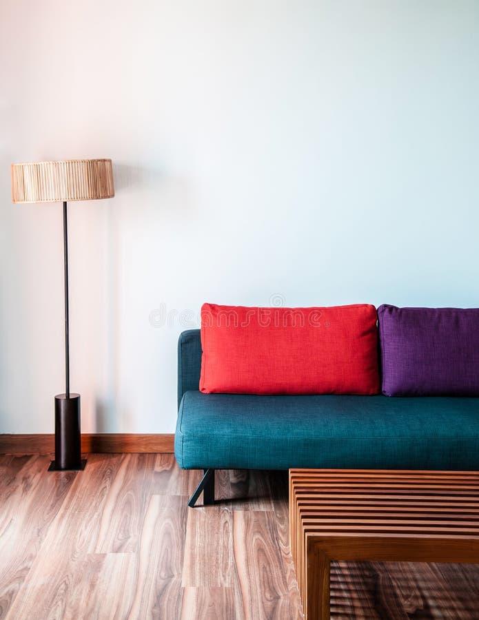 Sala de estar blanca con el sofá colorido moderno, la tabla de madera y l foto de archivo libre de regalías