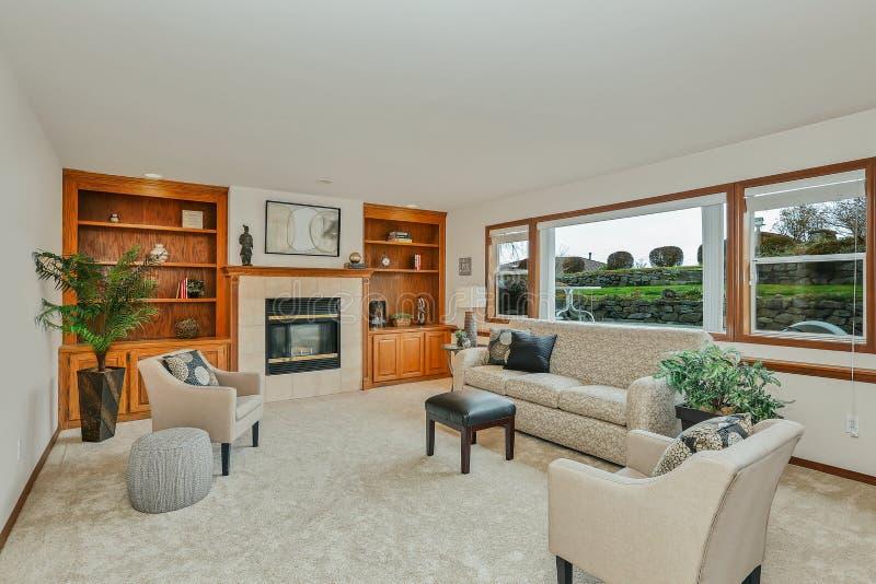 Sala de estar blanca tradicional clásica con los estantes de madera y las ventanas grandes fotos de archivo