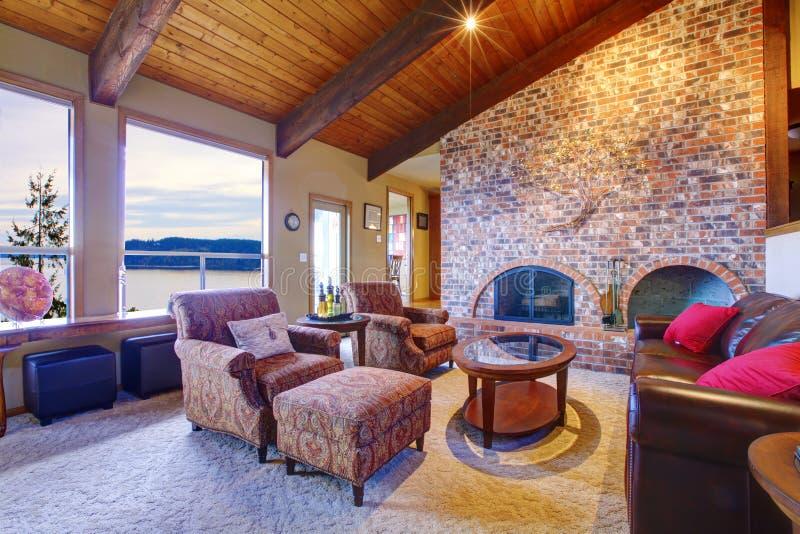 Sala de estar con el techo y la chimenea de madera. fotos de archivo