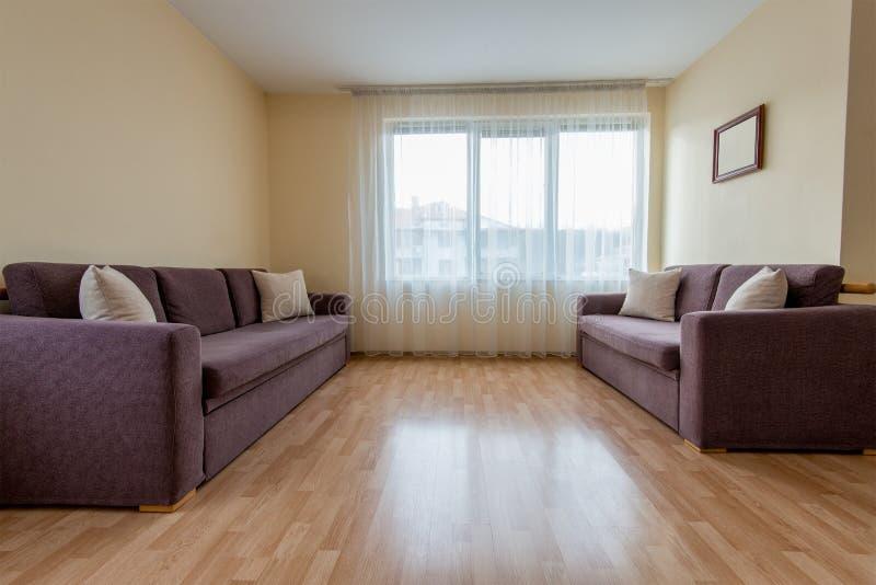 sala de estar con un sofá, las ventanas y las cortinas foto de archivo libre de regalías