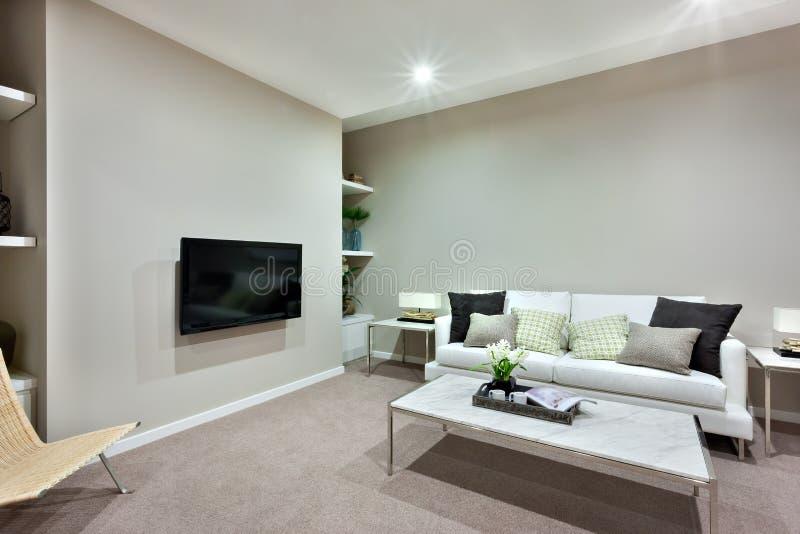 Sala de estar con una tabla blanca y los sofás con las almohadas de una casa lujosa imagen de archivo libre de regalías