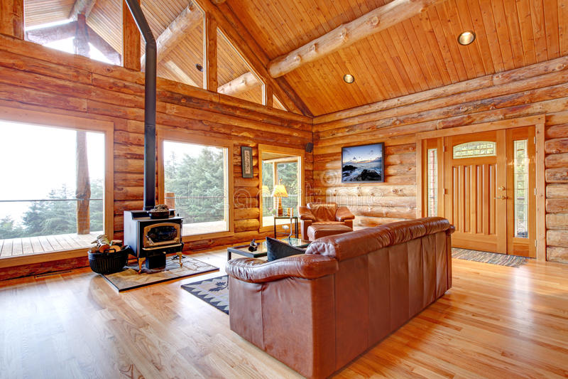 Sala de estar de lujo de la cabaña de madera con el sofá de cuero. imagen de archivo