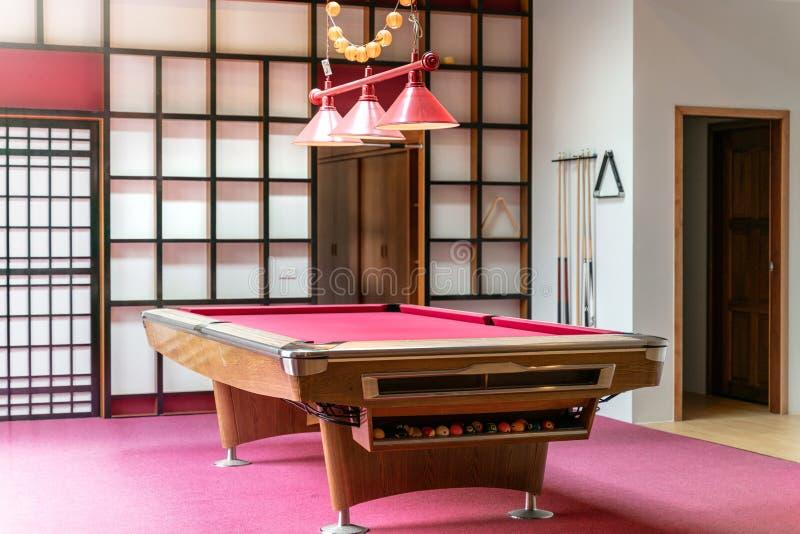 Sala de estar del diseño interior con la tabla de billar rosada en la casa imagenes de archivo