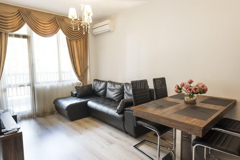 Sala de estar del espacio abierto Nuevo hogar Sitio con muebles marrones del tono del color Windows con las cortinas, la pa?er?a  imagenes de archivo