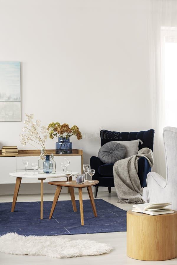 Sala de estar del gris y de los azules marinos interior con las mesas de centro y la butaca del terciopelo fotografía de archivo libre de regalías