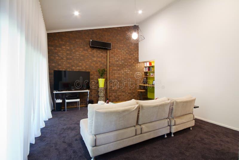 Sala de estar expuesta 70s renovada del apartamento de la pared de ladrillo fotos de archivo