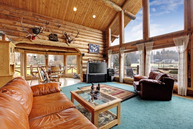 Sala de estar grande con área diining en casa de la cabaña de madera imagen de archivo