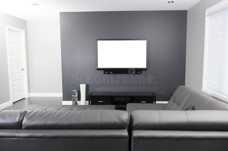 Sala de estar gris y blanca con el soporte y el sofá de la TV imagenes de archivo
