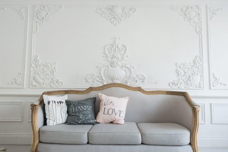 Sala de estar hermosa de Provance con el sofá sobre la pared de lujo adornada con los moldeados del estuco fotografía de archivo libre de regalías