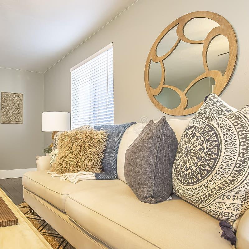 Sala de estar hermosa del cuadrado con las almohadas mullidas y la alfombra de la tabla de madera blanca del sofá fotos de archivo