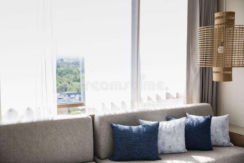 Sala de estar interior con el sofá, las almohadas y la lámpara del vintage imagen de archivo