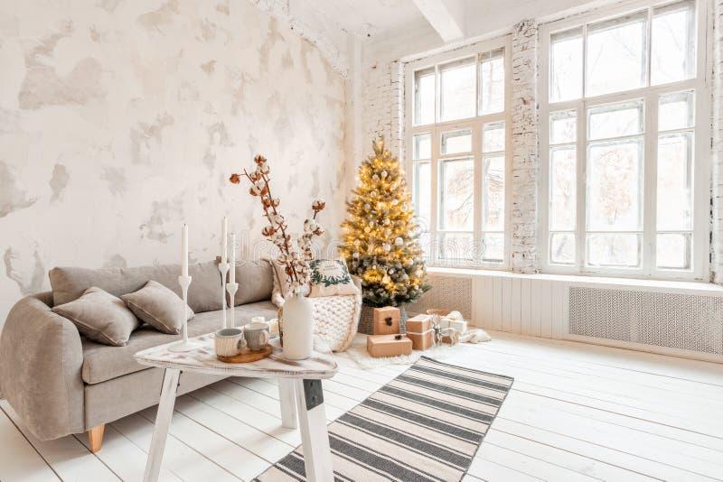 Sala de estar ligera con el árbol de navidad Sofá cómodo, alto Windows grande Pared de ladrillo blanca ligera fotos de archivo