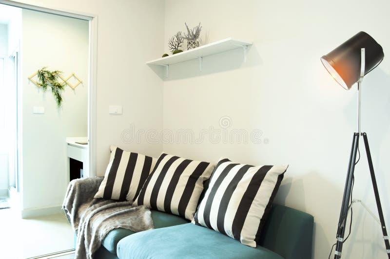 Sala de estar moderna con el sofá moderno con la lámpara del metal en casa imagen de archivo