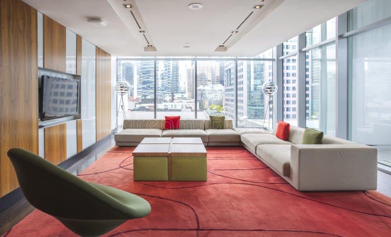 Sala de estar moderna con la opinión de los muebles y de la ciudad de la ventana fotos de archivo
