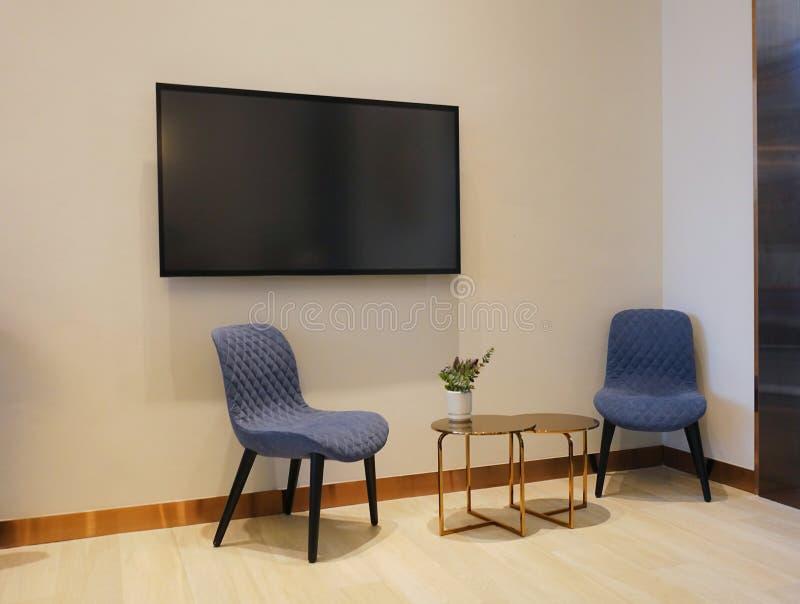 Sala de estar moderna de lujo con las sillas y tabla, pantalla en blanco TV, decoración del sofá en la noche Fondo casero del dis fotografía de archivo libre de regalías