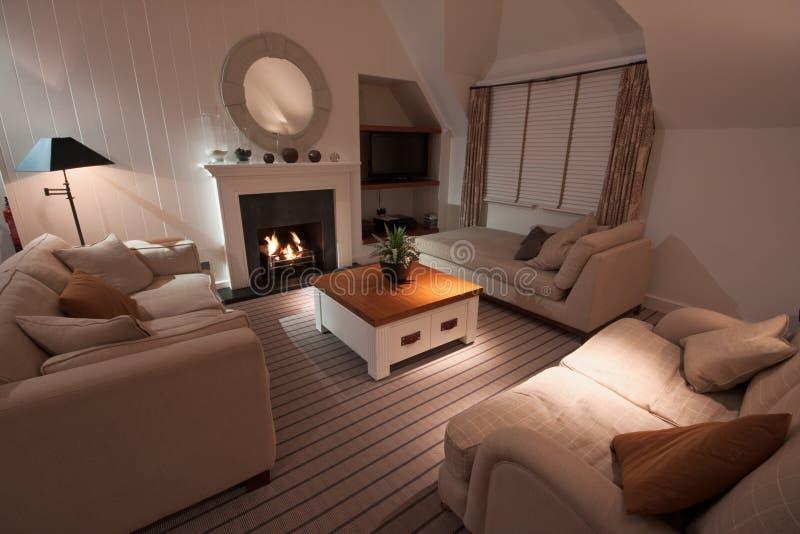 Sala de estar moderna lujosa con el fuego encendido foto de archivo libre de regalías