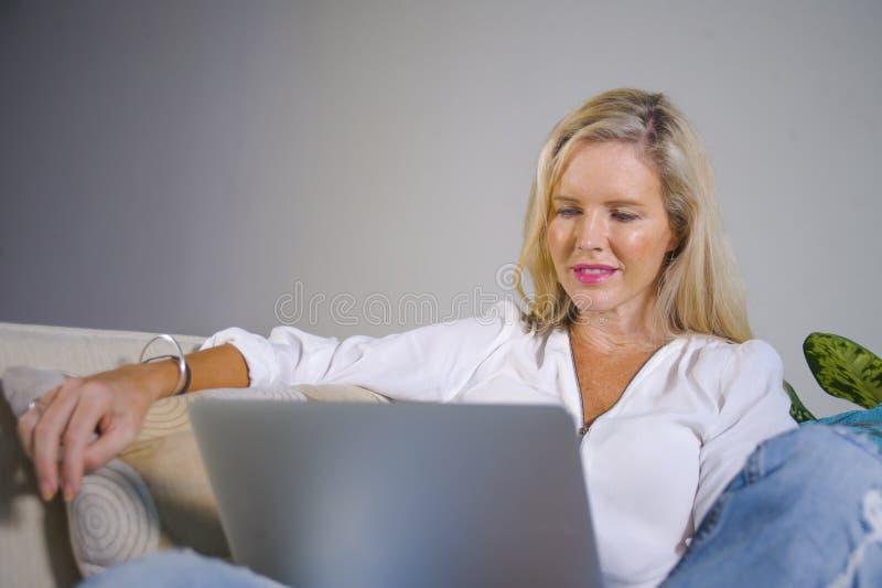 Sala de estar relajada temprana 40s de la mujer rubia elegante hermosa y feliz en casa usando Internet en comfortabl de trabajo d fotos de archivo libres de regalías