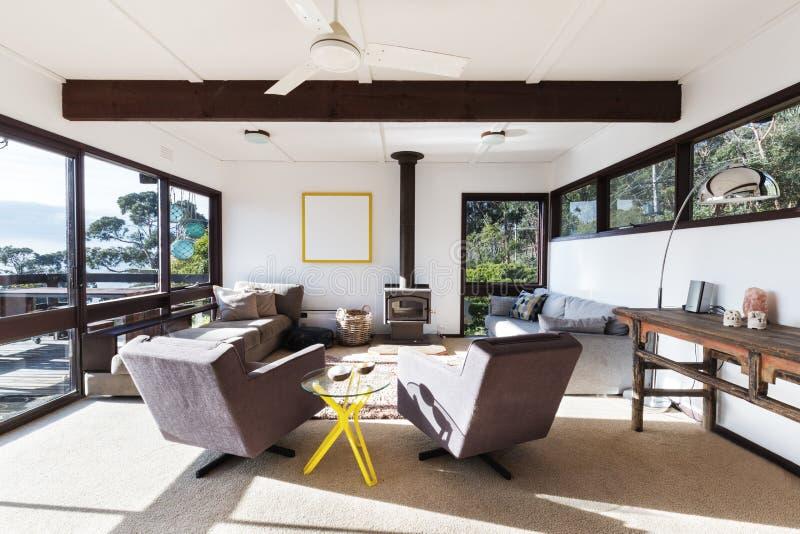Sala de estar retra enrrollada de la casa de playa con las sillas del estilo 70s fotografía de archivo