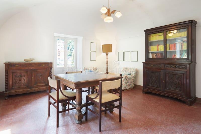 Sala de estar, viejo interior con la tabla y cuatro sillas imagen de archivo