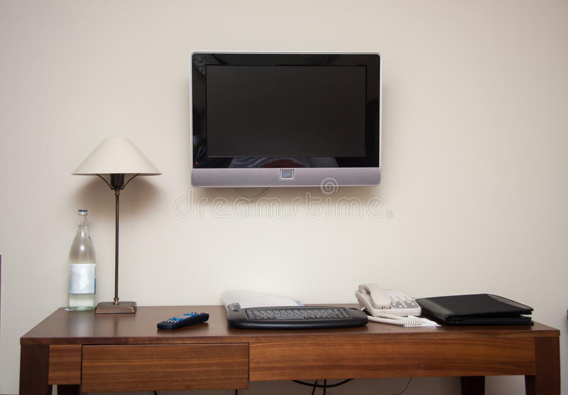 Sala de estudo com a lâmpada do telefone do teclado da mesa de escrita e o aparelho de televisão do lcd foto de stock