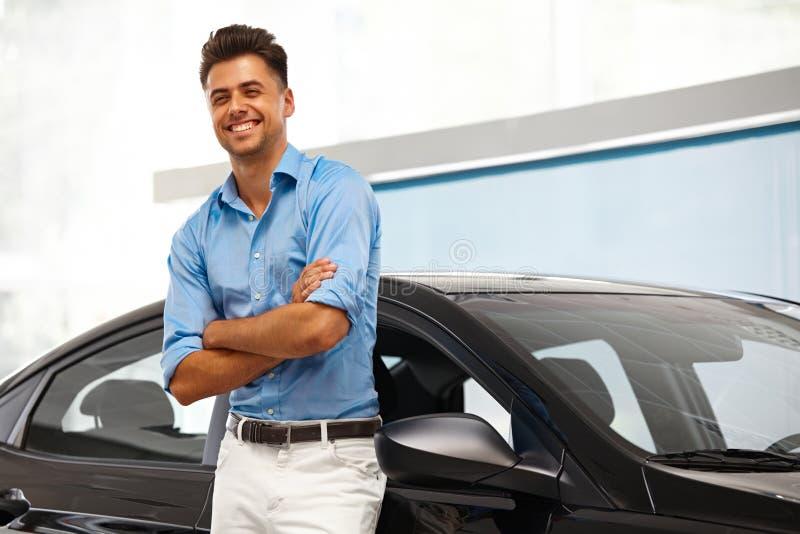 Sala de exposições do carro Homem feliz perto do carro de seu sonho fotos de stock royalty free