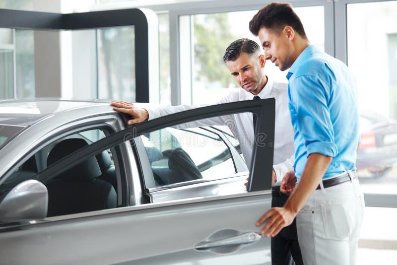 Sala de exposición del coche Distribuidor autorizado del vehículo que muestra a hombre joven el nuevo coche foto de archivo libre de regalías