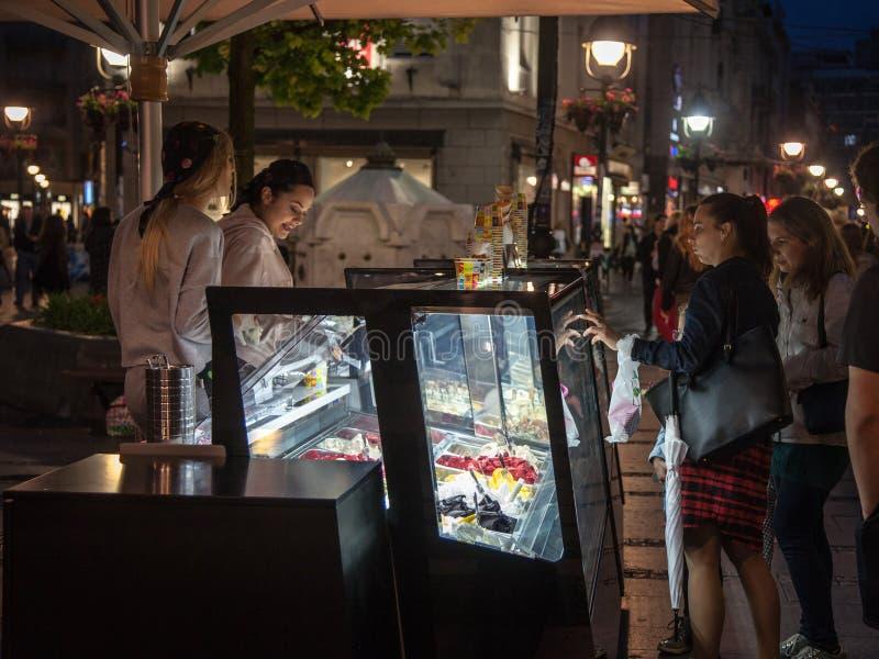Sala de helado que vende gelato italiano a las muchachas en una calle peatonal de Belgrado, Serbia, en la noche imágenes de archivo libres de regalías