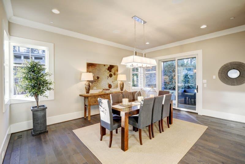 Sala de jantar bonita com tabela retangular e as cadeiras cinzentas foto de stock