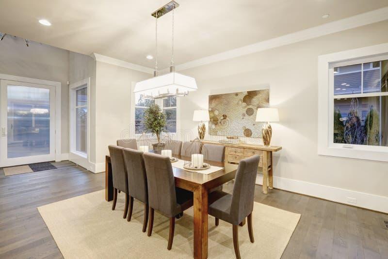 Sala de jantar bonita com tabela retangular e as cadeiras cinzentas imagem de stock