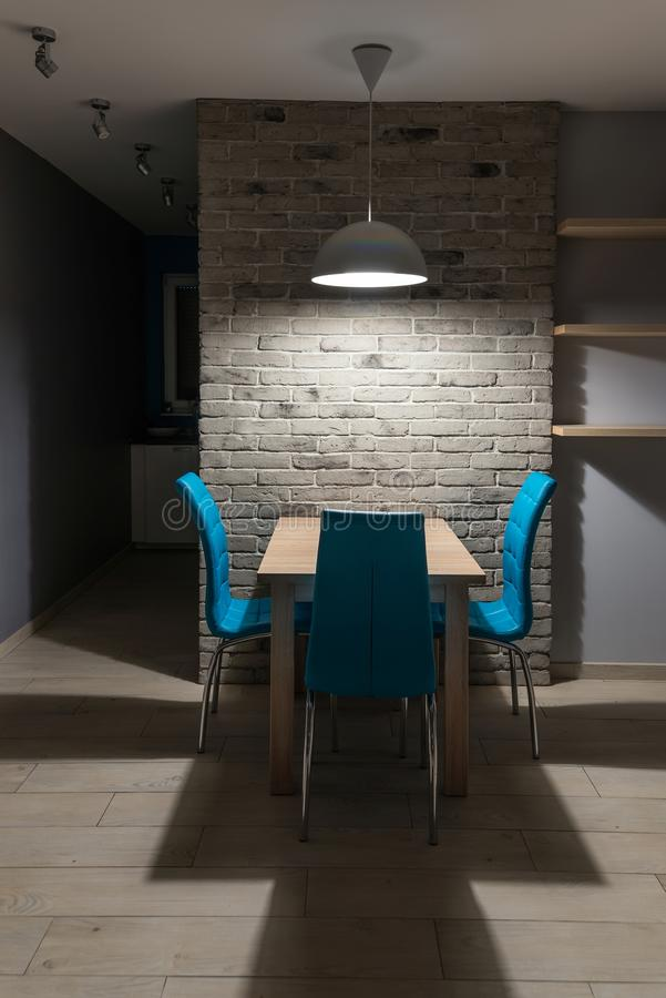 Sala de jantar com a tabela de madeira iluminada com suspensão acima da lâmpada imagens de stock royalty free