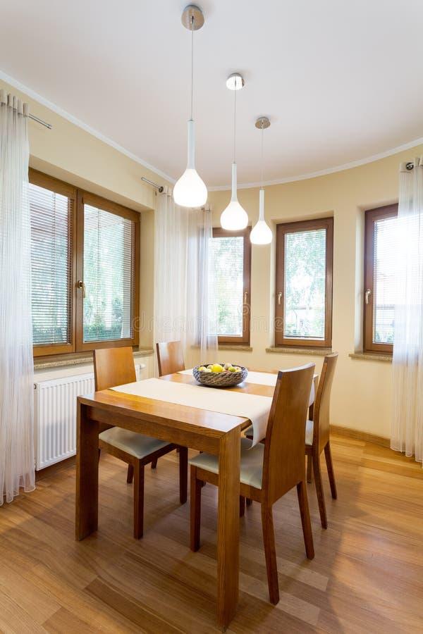 Sala de jantar confortável cercada por janelas fotografia de stock