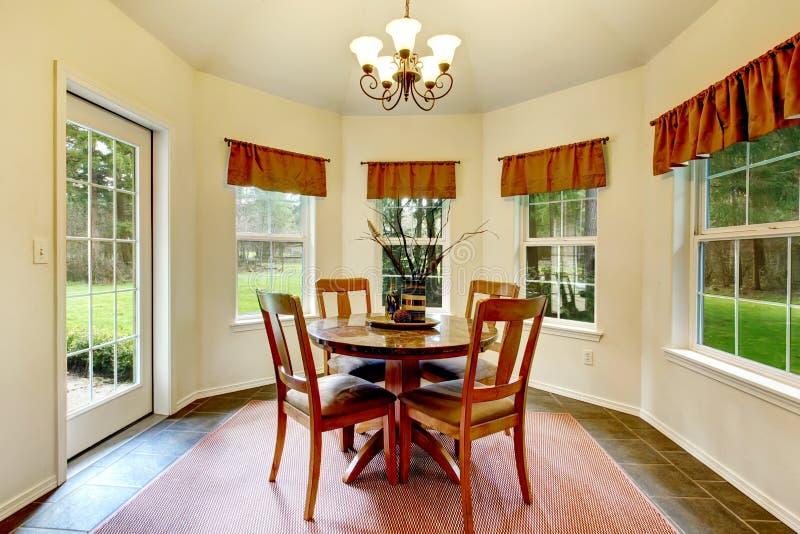 Sala de jantar do canto redondo com janelas francesas foto de stock