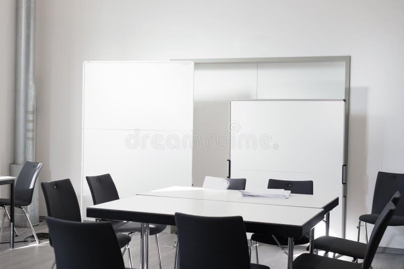 A sala de reunião vazia do escritório com cadeira, apresenta a placa branca fotografia de stock royalty free