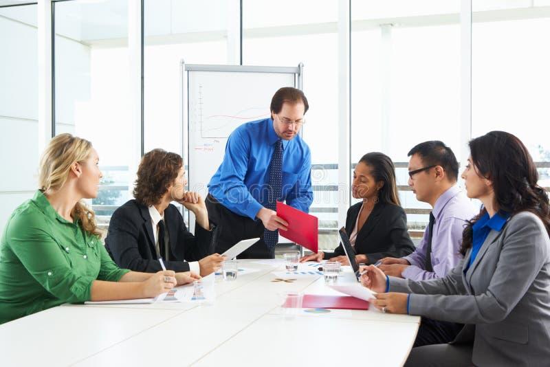 Sala de reunión de Conducting Meeting In del hombre de negocios imagen de archivo