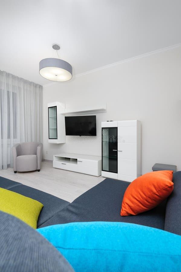 Sala de visitas branca com aparelho de televisão, cadeira e o sofá cinzento fotografia de stock royalty free
