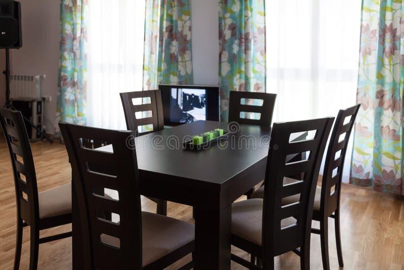 Sala de visitas com tabela, cadeiras e janelas, tevê imagens de stock